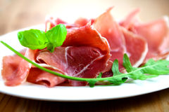 Dry cured ham. Close up of dry cured ham with arugula and basil royalty free stock photos