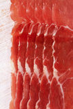 Dry cured ham slices on white wood background Royalty Free Stock Image