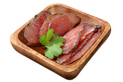 Dry-cured pork slices on wooden dish, over white. Stock Images