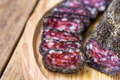 Dry-cured sausage coated with black pepper crust sliced on wood cutting board. Traditional Spanish or mediterranean delicacy. Royalty Free Stock Photography