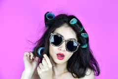 Dry and damaged hair with hair curlers rollers, Nervous girl try to styling her frizzy hair. Hair problems stock photo