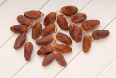 Dry dates are on branches, dried fruits are on white table royalty free stock images