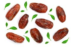 Dry dates decorated with leaves isolated on white background. Top view. Flat lay pattern.  Stock Photo