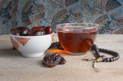 Dry dates fruits and cup of tea. Sweet date fruits, wooden rosary and black tea. Ethnic theme Stock Images