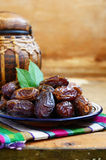 Dry dates on oriental ceramic plate with empty space Royalty Free Stock Photo