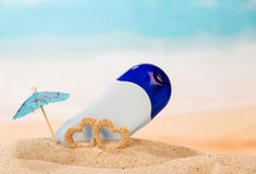 Dry deodorant, umbrella and hearts in sand against sea. Royalty Free Stock Photos