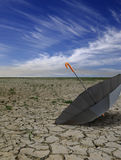 Dry deserted landscape with umbrella. Royalty Free Stock Photography