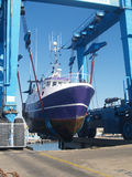 Dry dock hoist. A fishing boat being lifted in dry dock Stock Photo