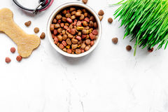 Dry dog food in bowl on stone background top view Stock Photo