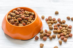 Dry dog food in bowl on wooden background. Close up Royalty Free Stock Images
