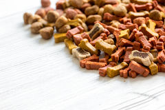 Dry dog food in bulk on wooden background close up Royalty Free Stock Photo