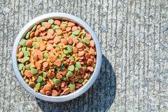 Dry dog food in in the stainless steel bowl Stock Image