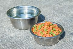 Dry dog food in in the stainless steel bowl and water Royalty Free Stock Images