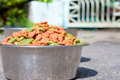 Dry dog food in in the stainless steel bowl and water Stock Photo
