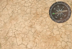 Dry earth and a compass Stock Images