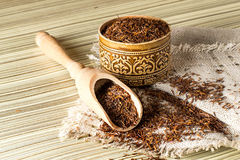 Dry ethnic african rooibos tea. In a wooden box and scoop on a linen cloth Royalty Free Stock Photo