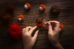 Hands with needles make bear with heart of wool royalty free stock images
