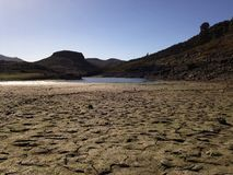 Dry field and lake in Gran Canaria. Dry field in the dam of las niñas, Gran Canaria, Canary islands, Spain royalty free stock photos