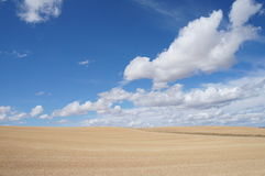 Dry field in Spanish village, dry grass, yellow, blue sky with white clouds. Dry field in Spanish village, landscape in autumn, dry grass and sunlight. blue sky royalty free stock photo