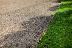 Dry field on a spring day, some tractor wheel print in ground, r stock image