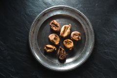 Dry figs on a tin plate on a gray stone Stock Photography