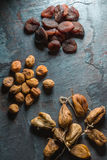 Dry figs, yellow and brown dried apricots on a gray stone Royalty Free Stock Photography