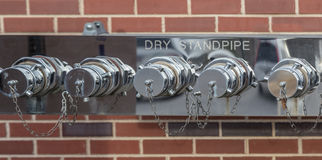 Dry Fire Department Standpipe. Dry Standpipe attached to the outside of a building so that a fire engine can supply water to the system in case of a fire stock photography