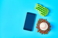 Dry food for pet near smartphone or tablet and rubber baseball ball and comb on blue background