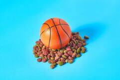 Dry food for pet and basketball ball on blue background