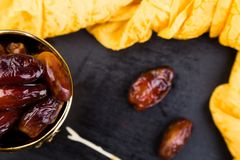 Dry fruit dates in golden cup near slate black heart. Copy space Stock Photos