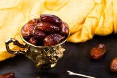 Dry fruit dates in golden cup near slate black heart. Copy space. Dry fruit dates in golden cup near slate black heart. Copy space Stock Image