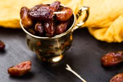 Dry fruit dates in golden cup near slate black heart. Copy space. Dry fruit dates in golden cup near slate black heart. Copy space Royalty Free Stock Photography