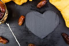 Dry fruit dates in golden cup near slate black heart. Copy space.Valentine Day. Dry fruit dates in golden cup near slate black heart. Copy space.Valentine Day Royalty Free Stock Images