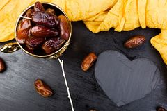Dry fruit dates in golden cup near slate black heart. Copy space.Valentine Day. Dry fruit dates in golden cup near slate black heart. Copy space.Valentine Day Royalty Free Stock Photography