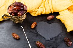 Dry fruit dates in golden cup near slate black heart. Copy space.Valentine Day. Dry fruit dates in golden cup near slate black heart. Copy space.Valentine Day Stock Photo