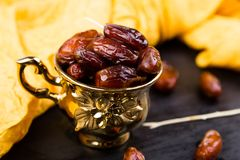 Dry fruit dates in golden cup near slate black heart. Copy space Royalty Free Stock Photos