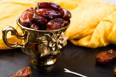 Dry fruit dates in golden cup near slate black heart. Copy space Stock Images