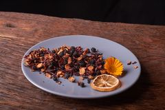 Dry fruit tea flower and lemon on plate. Nice red wood table. Concept of health food. Dry fruit tea flower and lemon on plate. Nice red wood table stock photos