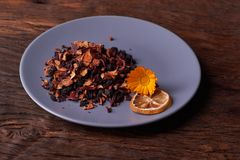 Dry fruit tea flower and lemon on plate. Nice red wood table. Concept of health food. Dry fruit tea flower and lemon on plate. Nice red wood table royalty free stock photo