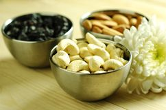 Healthy nuts. Nuts in brushed steel bowls on wooden table top stock photos