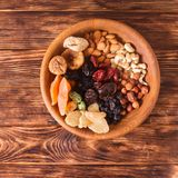 Dry fruits and nuts. In bowl on wooden table. Copy space background - close up healthy sweets Stock Image