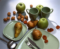 Dry fruits and table setting. Fruits, dry-fruits, plates, mugs, spoon, fork and knife on a table Stock Photos