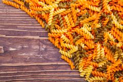 Dry fussili pasta of different colors. On a wooden background Stock Images