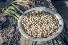 Dry grains of white beans lie on a wooden table in a white plate. Vegan food, animal protein substitute stock photos