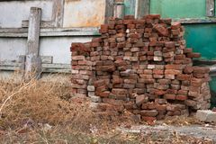 A pile of old bricks. Dry grass and old bricks stacked up against the fence royalty free stock image