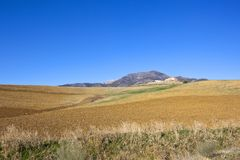 Mountains and arable fields of Andalucia. Dry grasses mountains and plow soil with a farm in scenic andalucia spain under a clear blue sky Stock Image