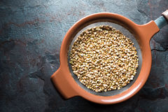 Dry green buckwheat in a sieve on a blue stone Royalty Free Stock Photo