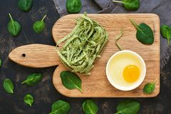 Dry green noodles with spinach and raw egg in a bowl on a dark background, top view Royalty Free Stock Photo