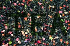 Dry green tea with flowers and pieces of fruit. Inscription on the background of tea top view stock photography