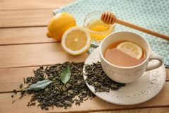 Dry green tea leaves and cup of aromatic beverage with lemon on wooden table stock photo